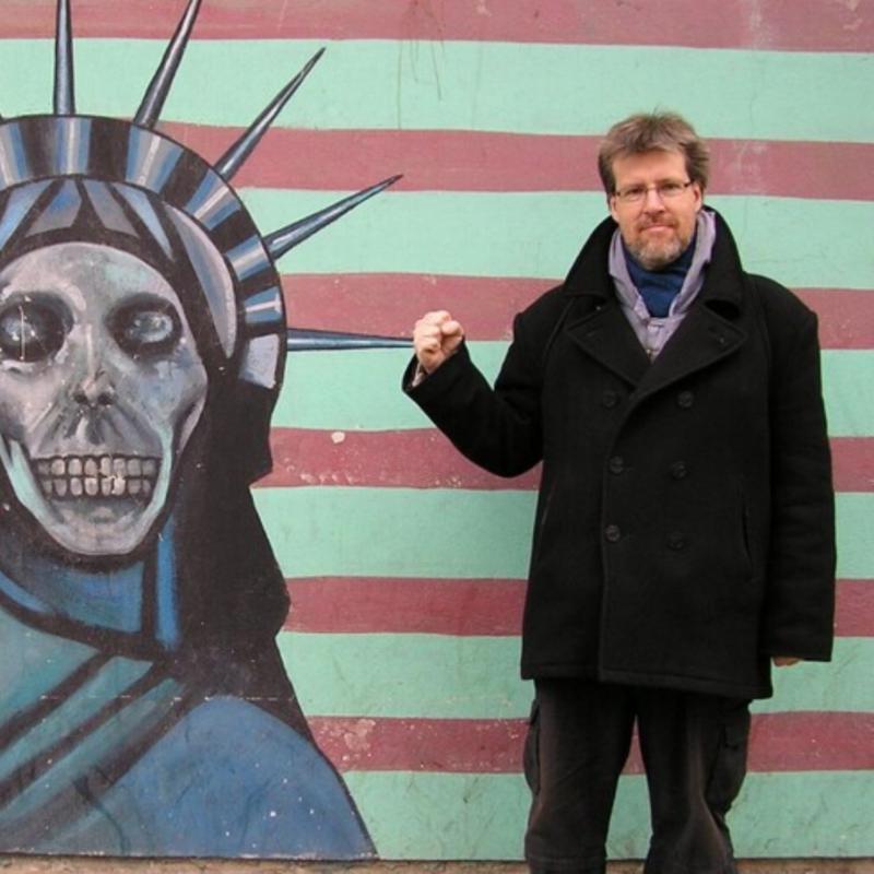 Pildil podcasti saatejuht seismas maalitud seina ees.